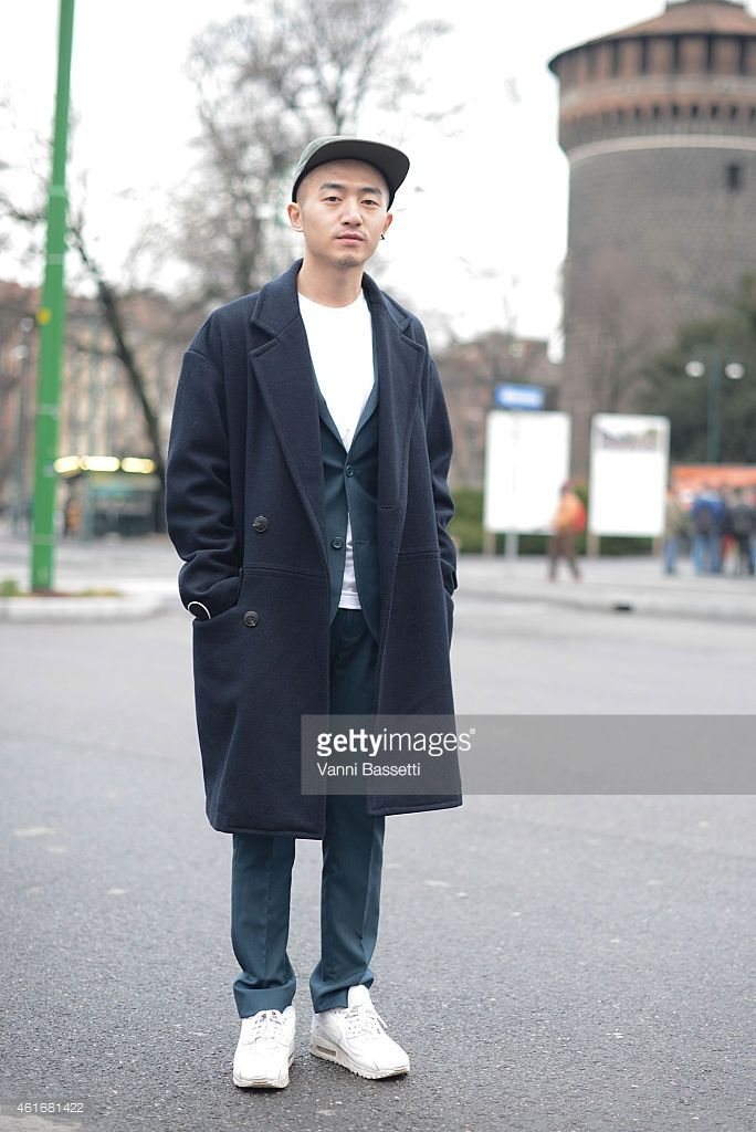 Evan Feng poses wearing a Topman coat, Prada suit and Nike shoes on January 17, 2015 in Milan, Italy.