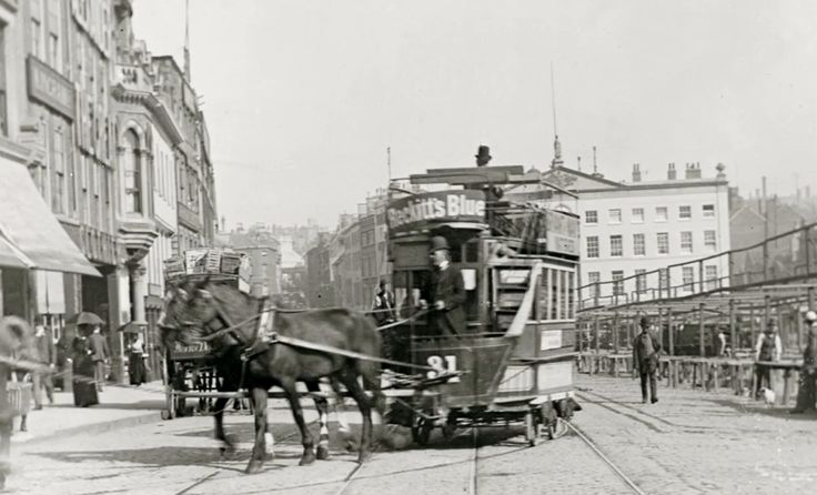 The Great Market Place in Nottingham, with a horse-drawn tram, market stalls and the old Exchange building in the background, 1890s.