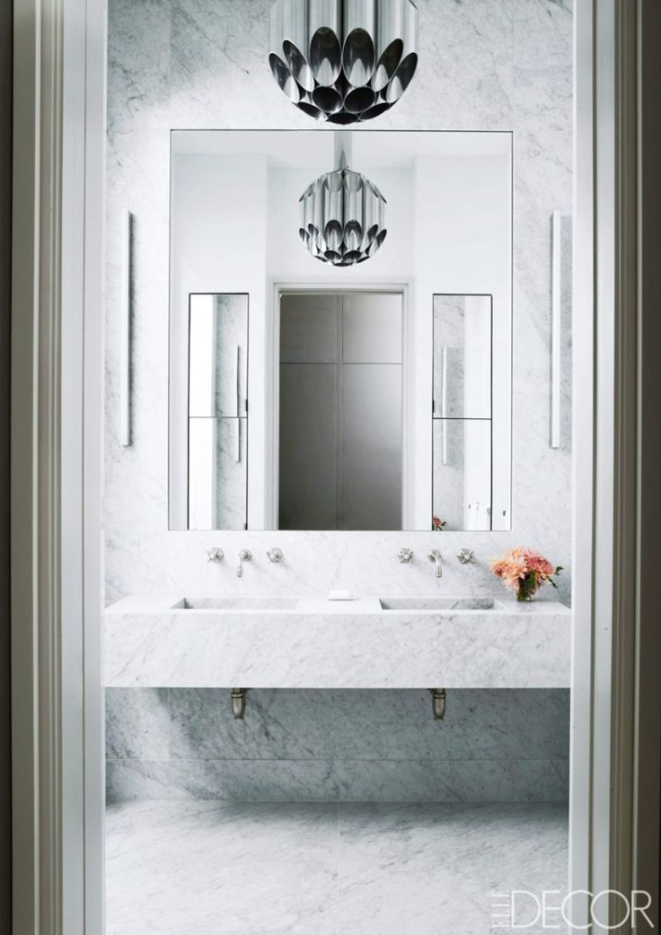 Rectangular-bathroom-mirror-A large, frameless mirror complements the elegant aesthetic of this marble master bathroom of a SoHo loft in New York City. A 1960s FontanaArte light fixture hangs above a cantilevered Carrara marble sink. Saved from:http://www.bocadolobo.com/en/inspiration-and-ideas/luxury-bathroom-mirrors/