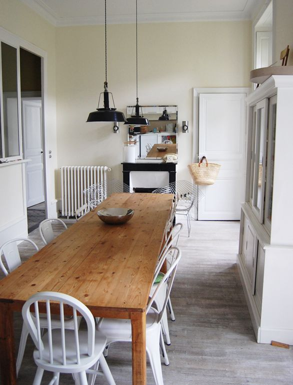 A mix of white-painted wood seating and metal chairs surround a long farm table in the kitchen.