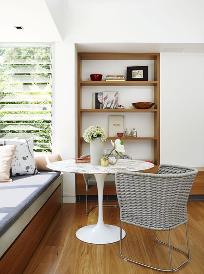 built-in window seat + wood shelving + pedestal table