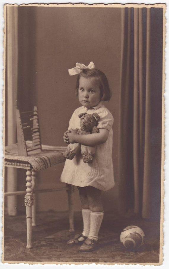 Little girl with a teddy bear and toys