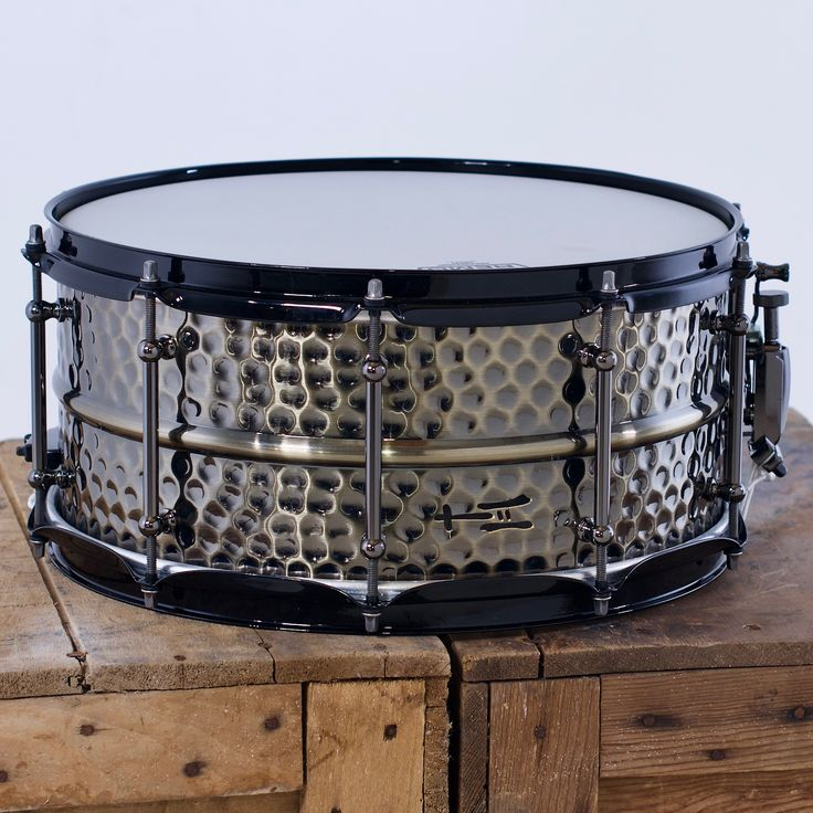 Black triple-flanged hoops alongside tube lugs, a traditional strainer and satin tension rods make for a beast of a snare drum! 6½x14; hammered brass. Available now! Add this drum to your arsenal today. #drum #snaredrum #customdrums