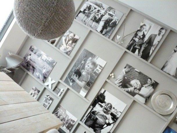 de latjes zijn aan de muur vast gezet in de zelfde kleur als de achtergrond met hierop wat accesoires en foto's