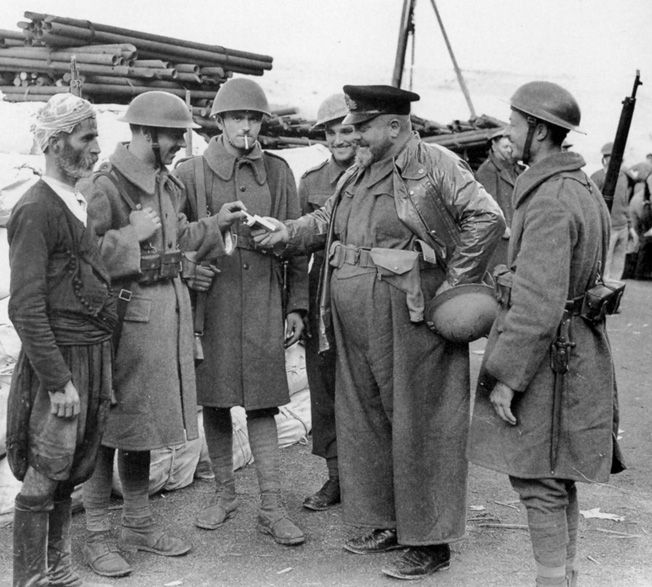 The hard-fighting Greek soldiers who participated in the defense of Crete were outfitted with a variety of uniforms and gear. Here they take a few moments in the company of an officer and a Greek civilian.