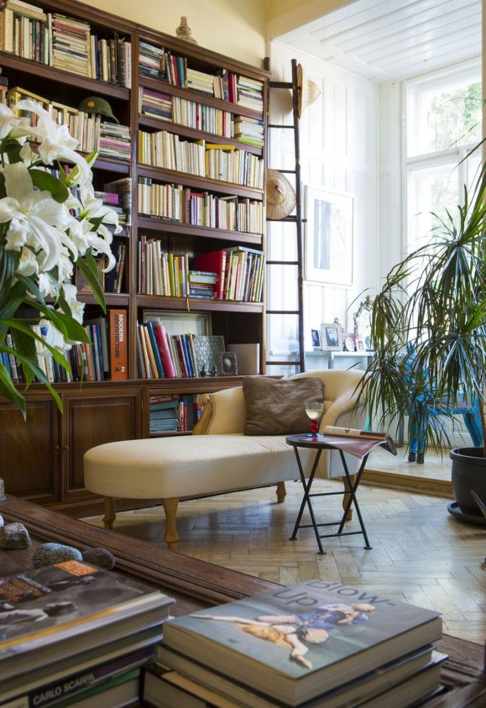 Living room features big wooden library, elegant cream sofa, wooden industrial coffee table and big window which brings light to the room. #livingroom #interior #elegant #desing #homedecor
