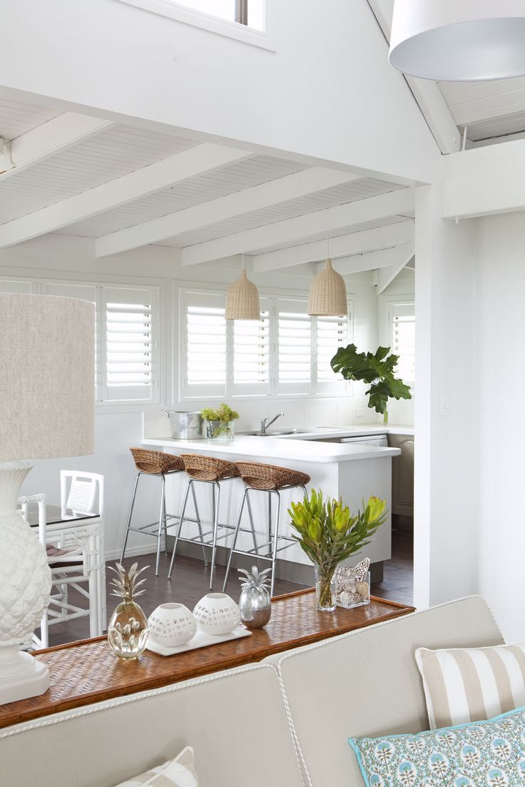 Very modern kitchen and living room with wide plantation shutters.