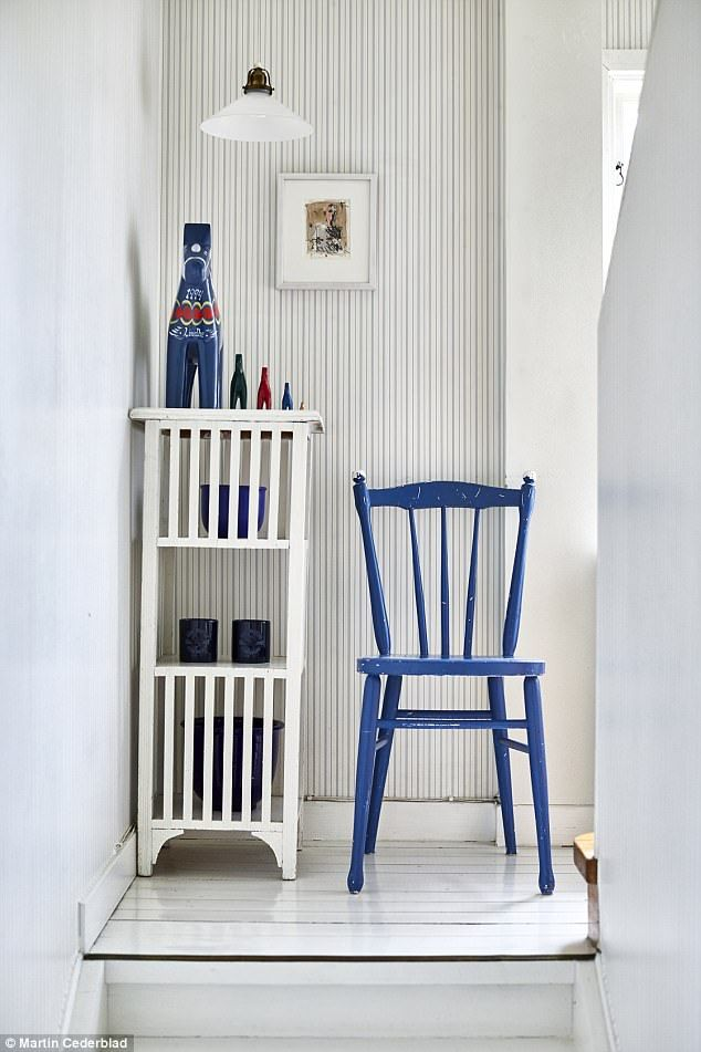 In the living room traditional Swedish dala horses decorate the white cabinet and add a splash of colour. For a similar chair, try Ercol (ercol.com)