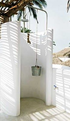 Outdoor shower with bucket for holding shower supplies