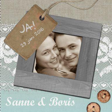Een vintage trouwkaart met grijze houten fotolijst en kant als achtergrond en versiering van knopen en labels.