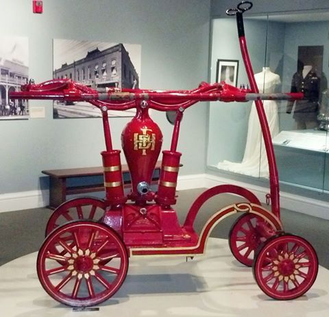 This Hand Operated Fire Engine was the first piece of fire fighting apparatus purchased by the Town of Hampton in 1884. It was constructed to propel a steady stream of water which firemen took turns pumping from wells, ditches and cisterns and the Hampton River