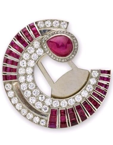 An Art Deco Ruby and Diamond Clip Brooch - Designed as a stylized pavé-set diamond crescent shape enhanced by lines of calibré-cut rubies and with cabochon-cut ruby terminal, mounted in platinum and gold. Circa 1930.