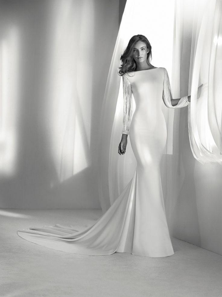 Relato: Elegante y sofisticado vestido de novia de estilo sirena y escote barco, con unas originales mangas con flecos que marcan la diferencia. Colección 2018 Pronovias