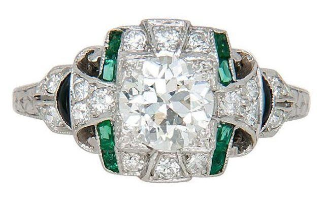 A 1930's Art Deco platinum, diamond, emerald and onyx engagement ring.