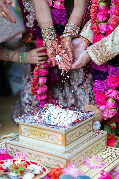 Wedding havankund with hands. Bride and groom and their parents say mantras and add herbs into the fire to bless the marriage.