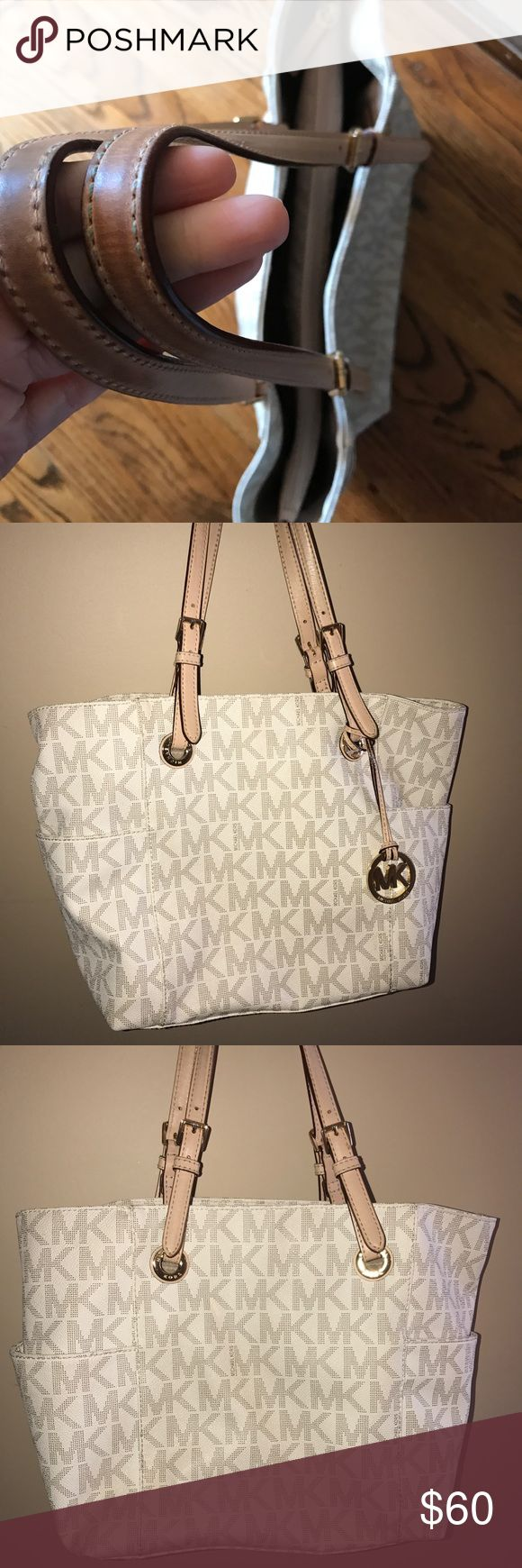 """Michael Kors Classic Jet Set Beige Tote Authentic Michael Kors Jet Set travel tote in a vanilla color designed with signature MK logos is elegantly detailed with gold-toned hardware giving the bag a classy, yet casual look. The bag has been used, but taken care of and is in good condition with some wear around the straps and with few red lipstick stains in the inside zipper pocket.  The inside has interior zipper pocket and 2 small slots. 9"""" shoulder drop. Exterior open slots on each side…"""