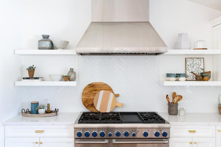 White floating shelves decorate a stainless steel vent ...