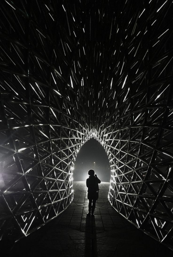 2016年11月14日,预报晚上会出现七十几年来最大的月亮。我陪朋友到上海南汇嘴拍月亮。但当晚是多云天气,所以我把注意力放在周围的景物上。在司南鱼的尾部,因夜间景观灯的照射,金属雕塑出现了象火花一样造型。我先直接拍了一张,中间的灯光太亮爆掉了,于是伸出左手放在画面中,来遮挡中间的光,拍出来的效果还是不理想,在准备离开是,听到有一男一女两个人边拍照边走近,于是我对他们说这里拍照的光影好,请女的站在这个位置,男的为她拍张,同时我也拍下了这张照片。