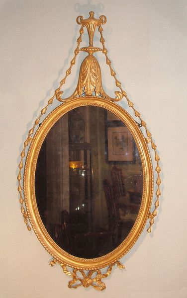 A late 18th Century Adam period carved giltwood Mirror with gadrooned oval frame, surmounted by acanthus leaf and urn pediment with leaf and swag decoration and carved ribbon bow below. Circa: 1780