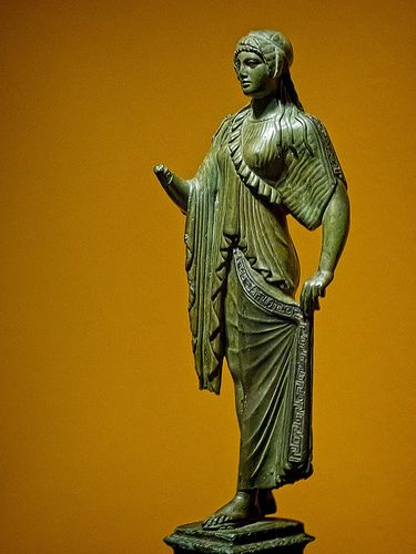 Roman figurine of a woman dressed in a tunic with a Maeander pattern in the style of archaic Greek korai figures of the 6th century BCE produced between 1st century BCE - 1st century CE and found in Verona, Italy bronze