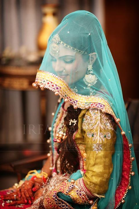 Indian bride wearing colourful bridal salwar and jewelry. #IndianBridalHairstyle #IndianBridalMakeup