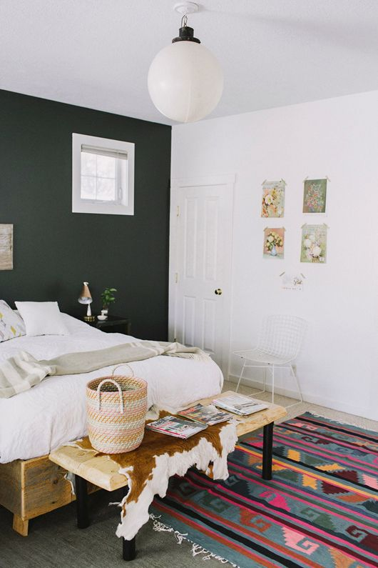 love this bedroom: rug, platform bed, one painted wall, and the flower prints casually taped to the wall. so good.