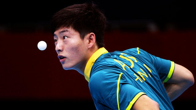 Justin Han of Australia serves against Mawussi Agbetoglo of Togo during their men's singles table tennis match on Day 1 of the London 2012 Olympic Games.