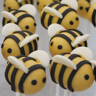 I think these are cake pop bumble bees. I'm not a huge cake pop fan but the design would easily transfer for fondant icing bees!   Just noticed the white chocolate Milky Way buttons for wings! Genius!!