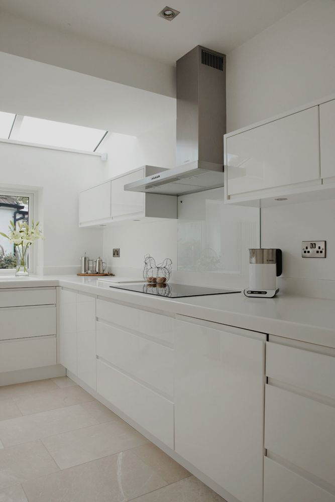 Minimal white gloss kitchen with solid surface worktops p