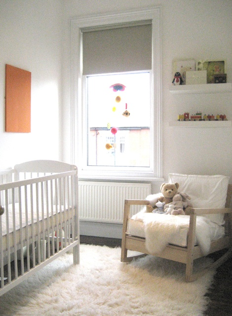 Mobile in the window/big fluffy rug. Must-haves for a cozy nursery.