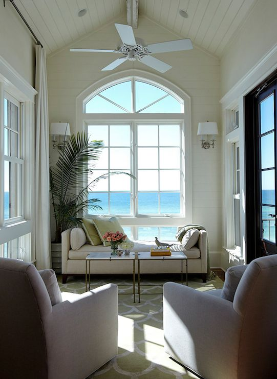Fantastic sunroom design with ocean view, mushroom linen settee, brass accent tables with marble tops, green rug, and cathedral ceiling.