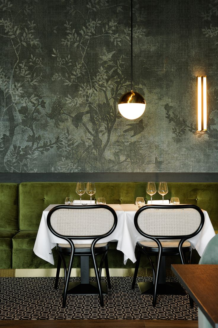Wallpaper, green velvet bench seating and bentwood chairs