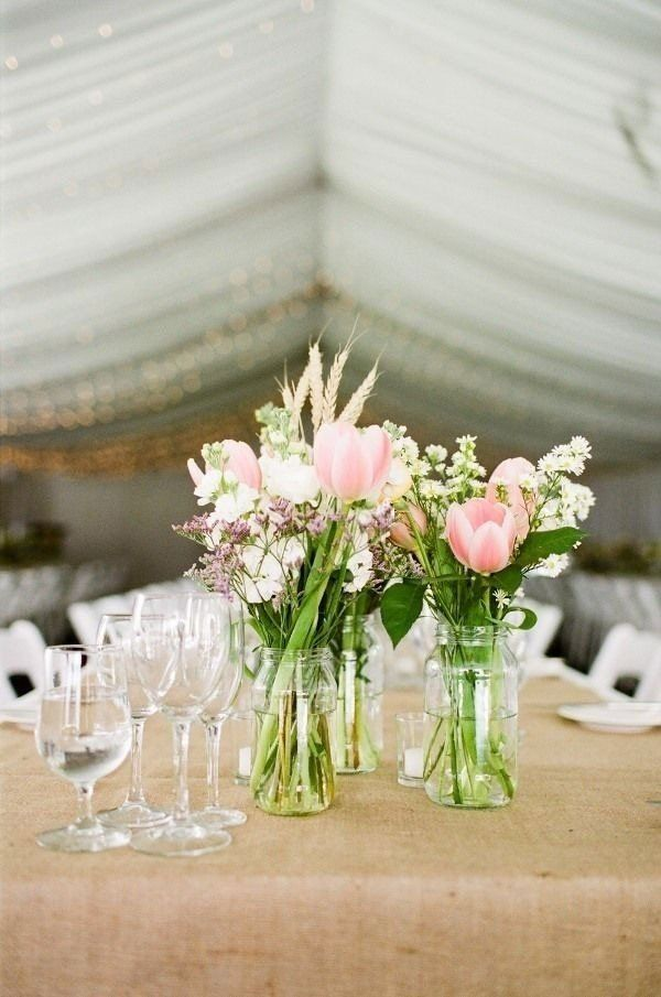 reception centerpiece featuring light pink tulips in Mason jar inspired vases