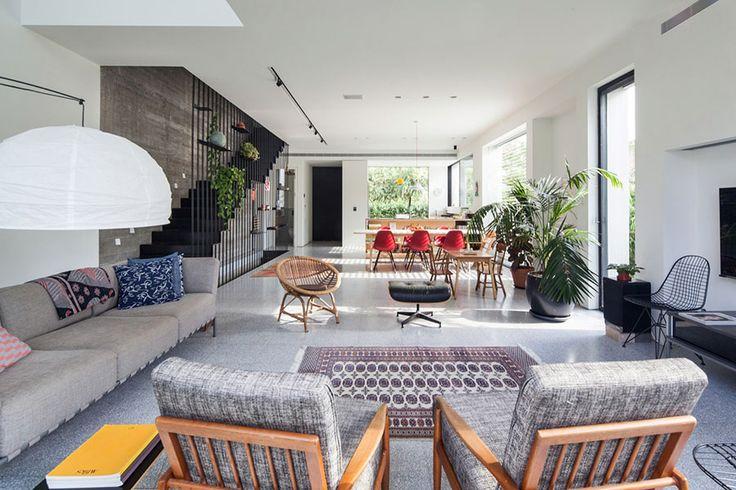 Decoração moderna com portas de vidro, poltrona cinza, tapetes, plantas, mesa de madeira, cadeiras vermelhas e iluminação natural.