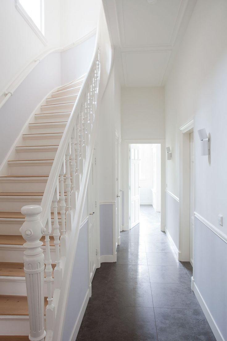 Witte hal met klassieke trap met houten treden