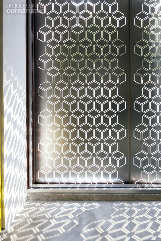 Personagem principal da obra, o revestimento de chapas metálicas (Ingecold) também leva a assinatura do Superlimão Studio. As placas cobrem todo o anexo de vidro erguido nos fundos da casa. Em dias claros, as sombras dos recortes se espalham por pisos e paredes, como neste detalhe.