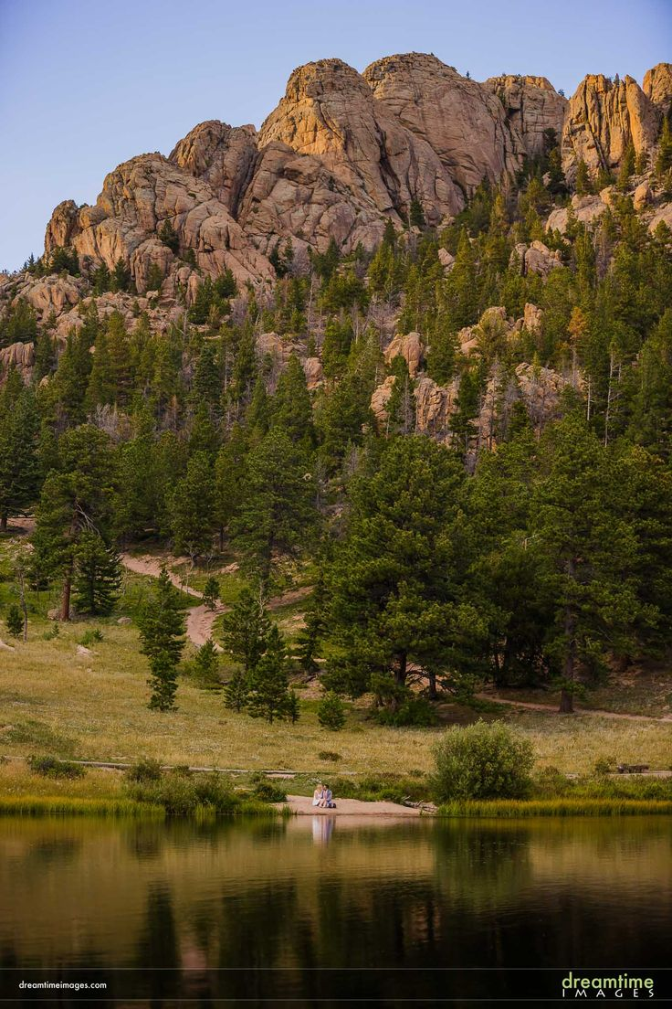 A bride and groom relax on a lakeside beach in Estes Park