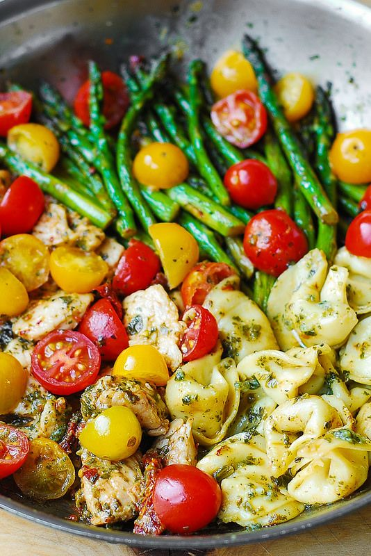 An easy healthy chicken dinner recipe, yellow and red grape tomatoes, asparagus, sun-dried tomatoes, pesto, tortellini, chicken