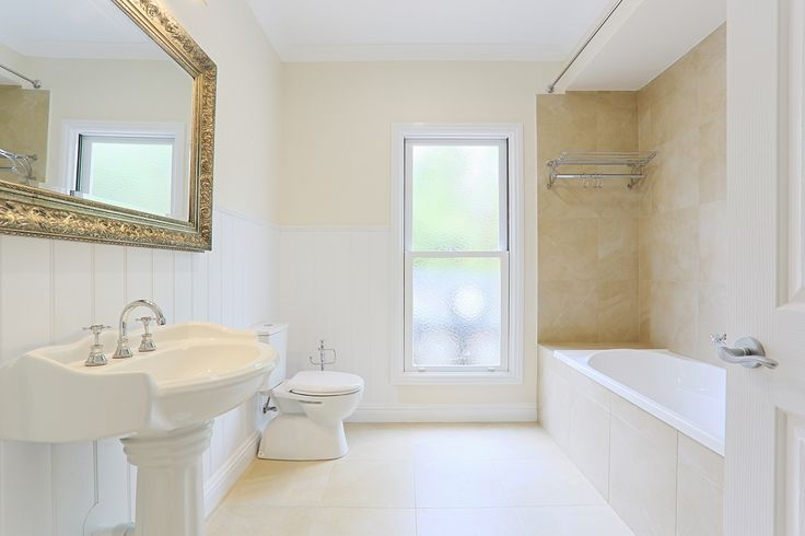 An expansive bathroom boasting beautiful traditional details and soft natural tones. A bathroom renovation by Smith & Sons.
