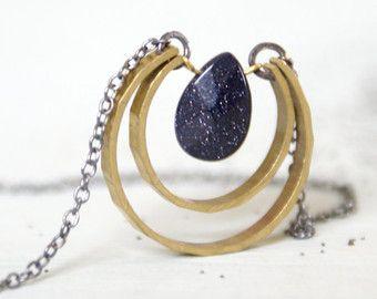 Een daling van de gefacetteerd kwartskristal hangt van geoxideerd zilver ketting binnenkant van een geciseleerde messing wassende maan. Deze