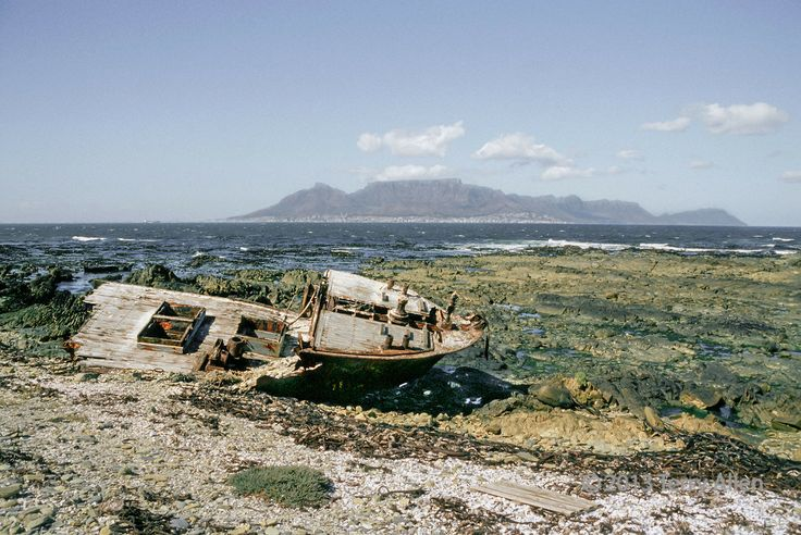 Wrecked fishing boat on Robben Island, Cape Town in background, South Africa