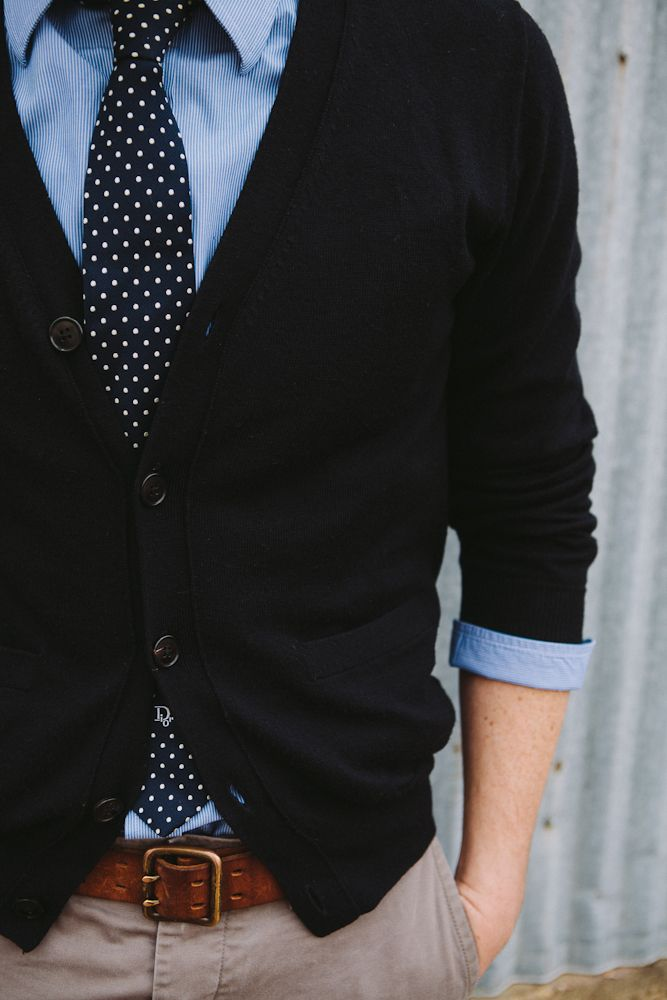 blue oxford. black cardigan. navy blue tie w/ dots. khaki pants. brown belt. office casual style.