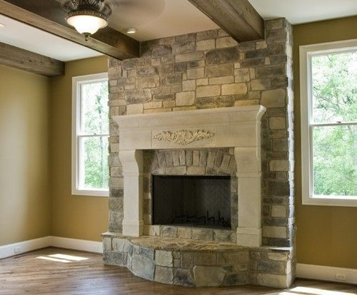 Fireplace. White wood mantle. Raised hearth.  Grey stone to ceiling.