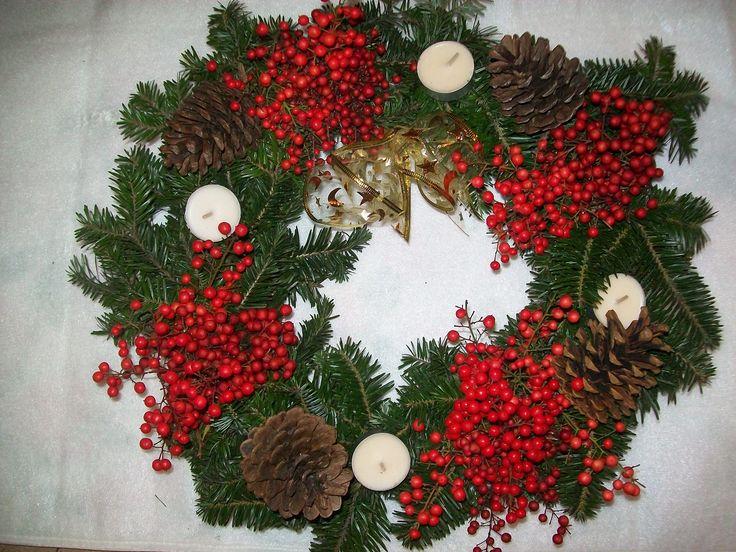 corona decorata con pino, bacche di Nandina, pigne e candeline bianche