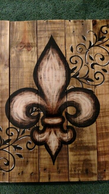 Brown fleur de lis painted on wood pallet board with swirls