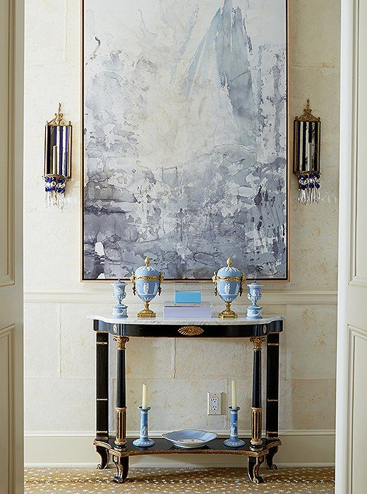 An abstract modern painting in shades of gray serves as a contemporary counterpoint to a gilded French console table topped with antique Chinoiserie urns and candlesticks.