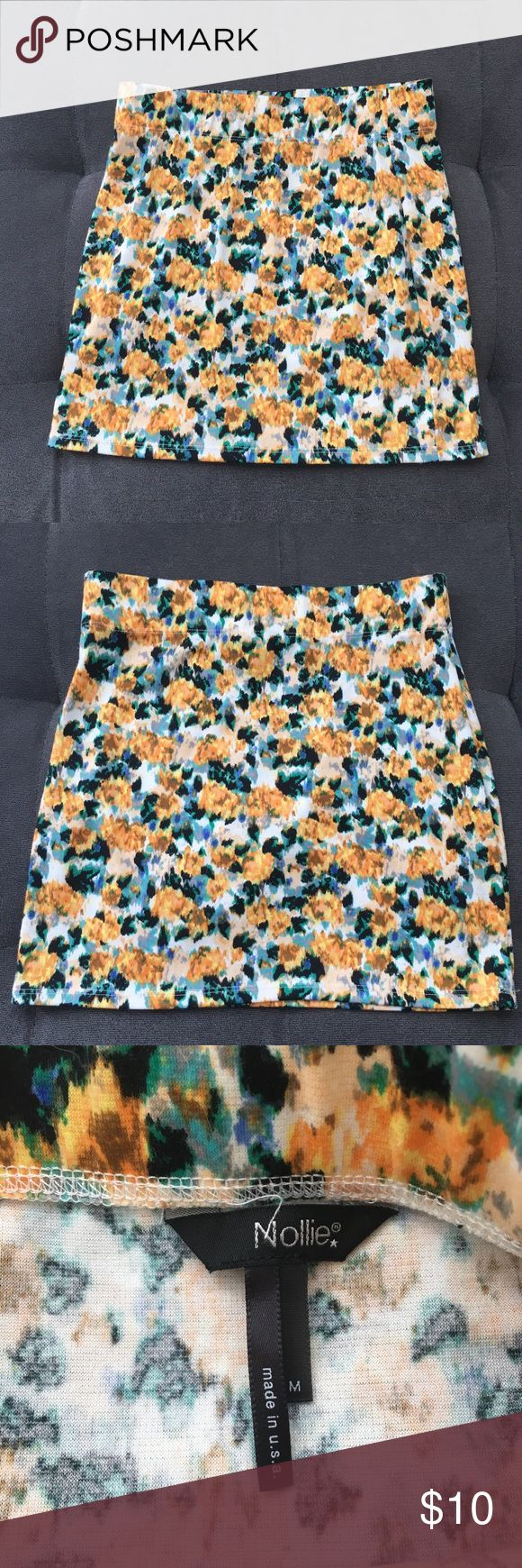 """Nollie PacSun Floral Mini Skirt Juniors Medium Nollie PacSun Floral Mini Skirt. Elastic waist. White, green, black, blue, yellow, orange colored.   Size: Juniors Medium  About 15"""" length (top to bottom)   Good pre loved condition. Please see last pic for small piling area.   Bundle fav items for a personal discount. Offers are always welcome, too! No trades. Thank you! (11)  Tags: summer, dance, bodycon, floral, back to school Nollie Skirts Mini"""
