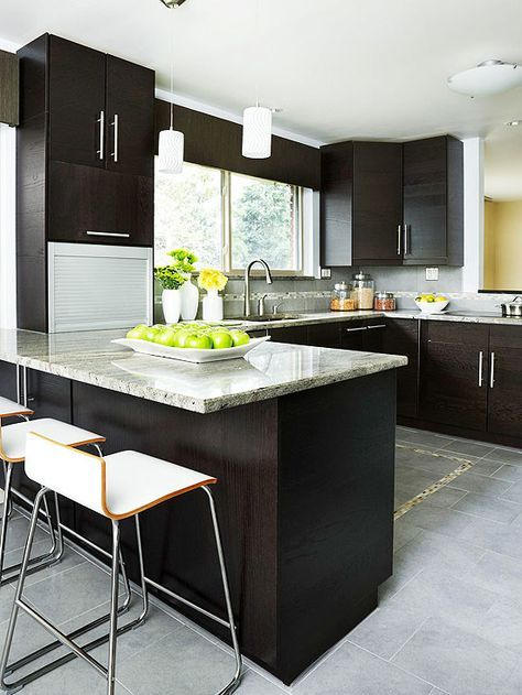 Rich espresso cabinetry features clean lines and fuss-free chrome pulls. Cool tones are added in the granite countertops and stone floor.