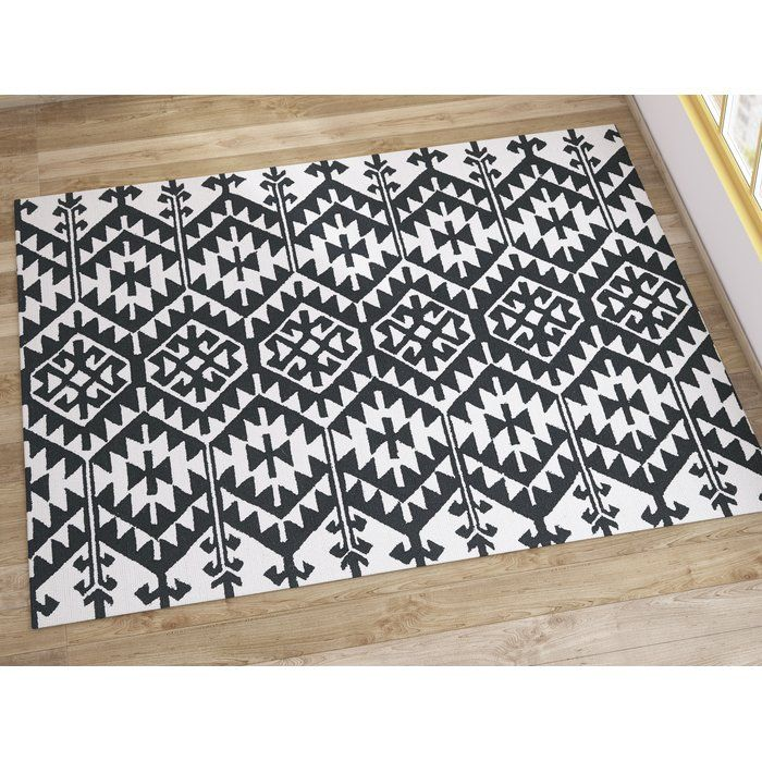 Southwestern style abounds with the Handmade Black/Ivory Rug, an artful addition to any aesthetic in your well-appointed home. Use it to anchor a crisp contemporary ensemble in the den or add it to the entryway to round out a bold boho look. Its geometric motif adds a pop of pattern your decor while its 2-tone hue blends effortlessly into any color pallet. Add it to the guest room to level out a monochromatic look then pair it with a sunburst wall mirror for a dynamic display. Its…