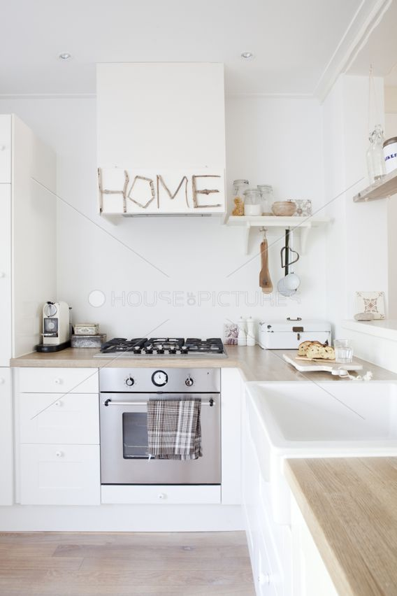White cupboards with pale butcher block counters and deep sink and hanging utensils under shelves